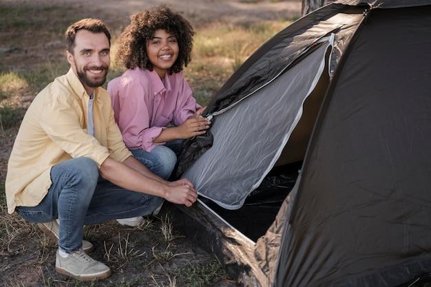 Пара на открытом воздухе, устанавливая палатку вместе