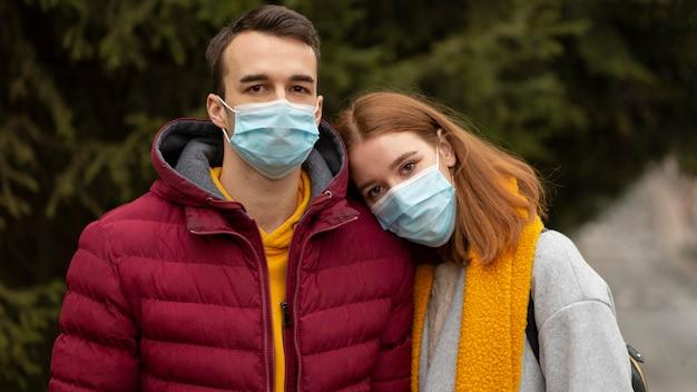 Coppia all'aperto insieme indossando maschere mediche
