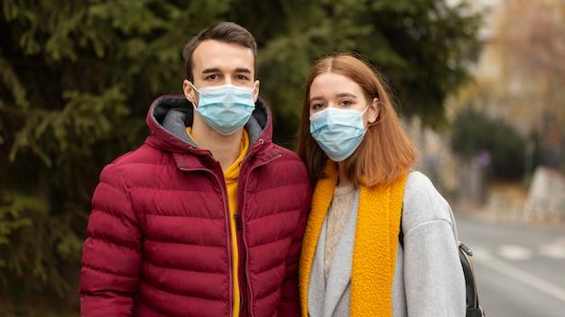 Coppia all'aperto indossando maschere mediche