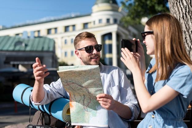 屋外のバックパックと地図のカップル