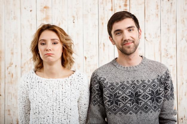 Пара над деревянной стеной человек улыбается, девушка грустно.