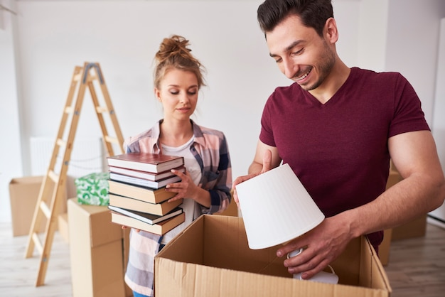 Couple packing books and lamp to the boxes