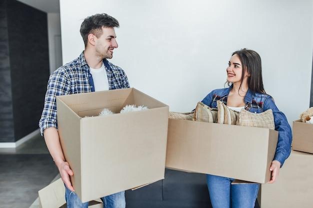 たくさんの段ボール箱の中に荷物を詰めるカップル