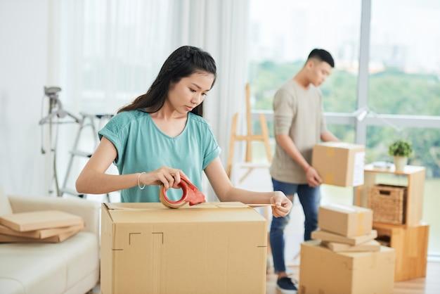 移動するボックスを梱包するカップル