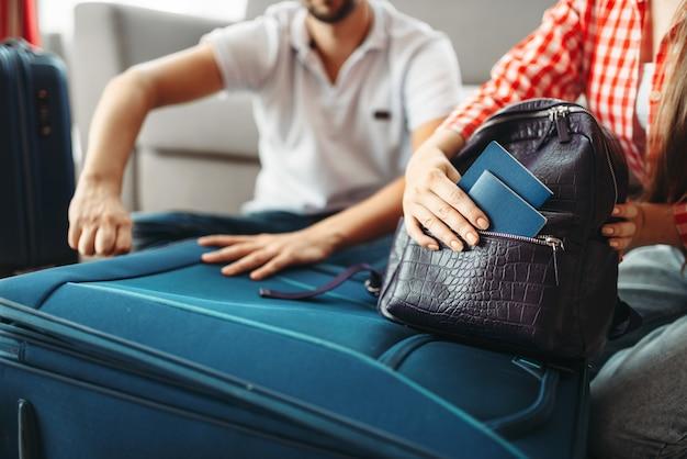 カップルがスーツケースを梱包して書類を取る