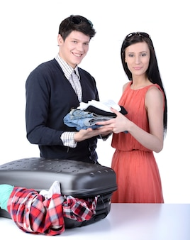 Couple packs up suitcase with clothing for travel.
