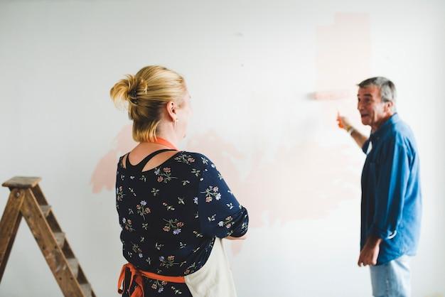 パステルカラーのピンク色の壁を塗るカップル
