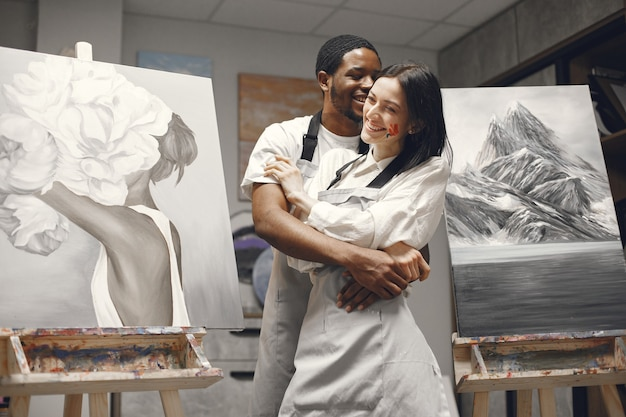 Couple in a painting class embracing.
