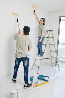 Пара красит стены комнаты