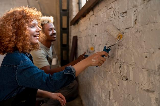 Пара вместе красит стены своего нового дома