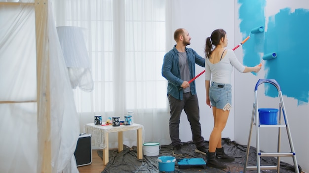 Couple painting wall using roller paint brush. painting wall with blue paint. color change. renovate, renovation, construction. apartment redecoration and home construction while renovating and improv