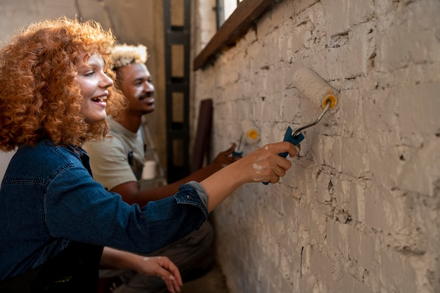 Couple painting the walls of their new home together