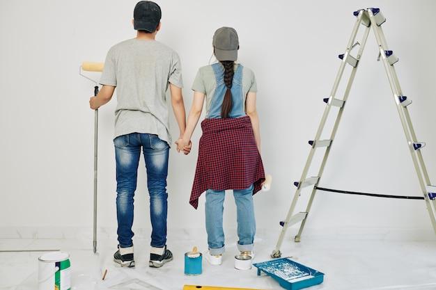 Пара вместе красит стены