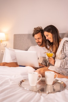 A couple in pajamas looking at the computer in the breakfast of coffee and orange juice in the hotel bed, lifestyle of a couple in love.