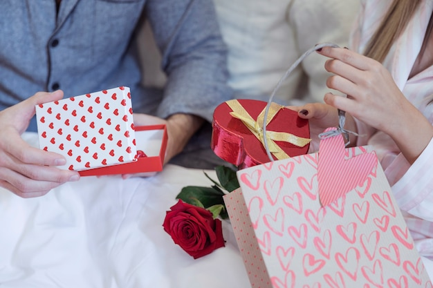 Couple in pajamas sitting on bed with gifts