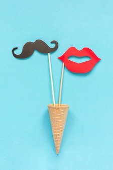 Couple paper mustache, lips props on stick in waffle cone on blue. concept valentine's day