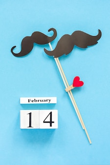 Couple paper mustache props fastened clothespin heart and calendar february 14