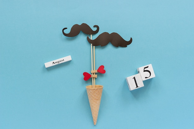 Couple paper mustache props fastened heart in ice cream cone and calendar 15 august. concept homosexuality gay love