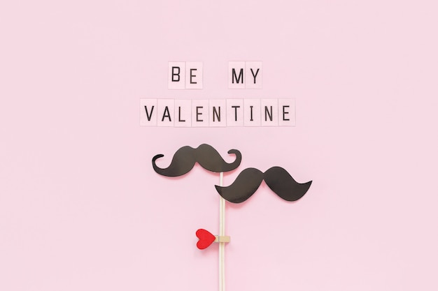 Couple paper mustache props on stick fastened clothespin heart and text be my valentine