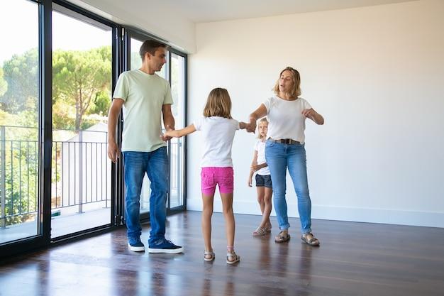 Coppia di genitori e due bambini che si godono la loro nuova casa, in piedi nella stanza vuota e tenendosi per mano, ballando