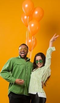 Coppia alla festa divertendosi e tenendo palloncini