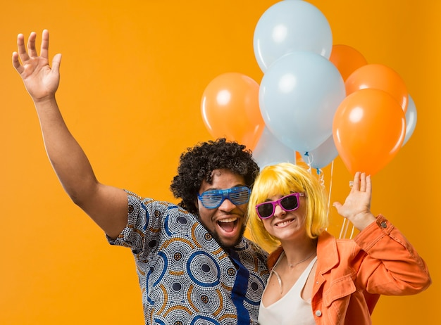 Couple at party having fun and holding balloons