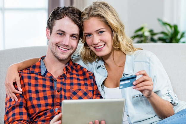 Couple paying with credit card on the couch