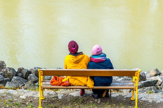 Couple of people in colorful clothes sitting on a wooden yellow bench facing a white wall