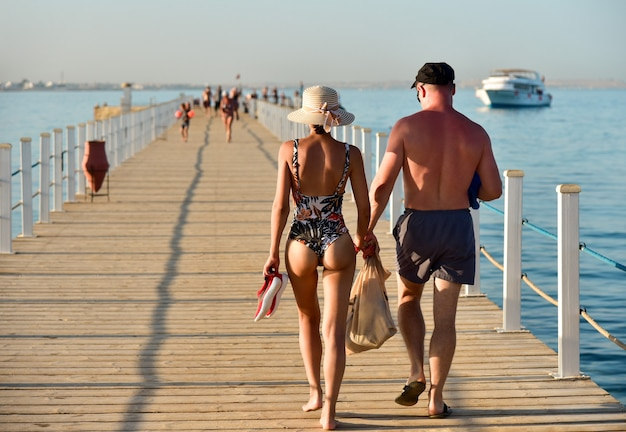 A couple of people walking on a pier in swimsuits watching and snorkeling.