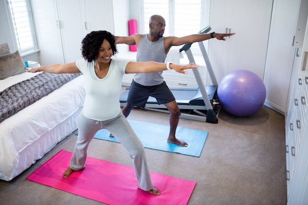 Couple performing exercise in bedroom