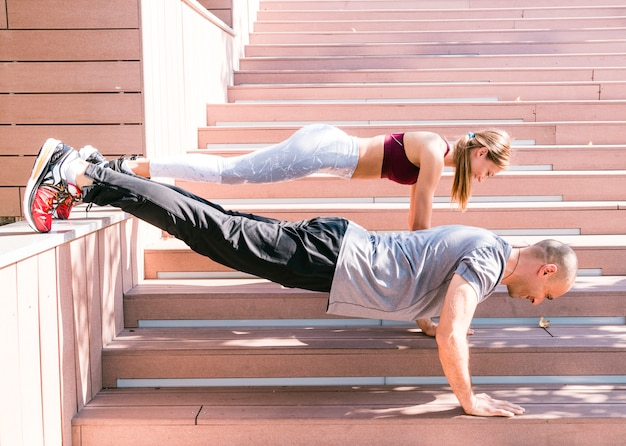 Couple performing push up exercise on staircase in sunlight