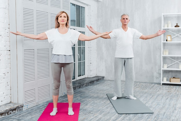 Couple performing yoga by outstretching arms standing on yoga mat