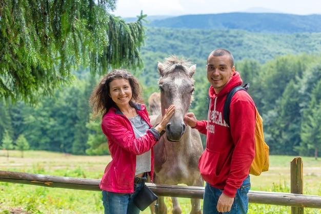 Пара, лаская лошадь через деревянный забор в сельскохозяйственных угодьях гористой местности.