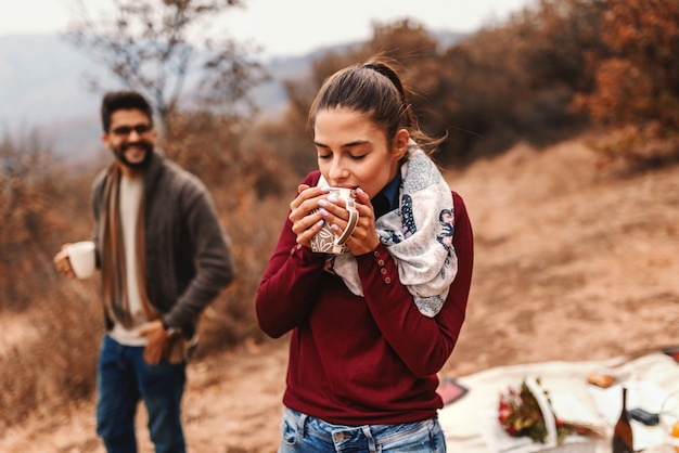 Couple at picnic. woman standing and drinking tea while man standing in background. autumn time.