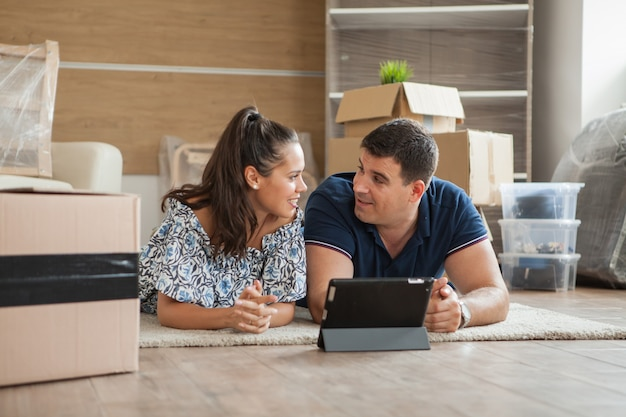 タブレットと一緒に装飾を計画し、リビングルームで家に引っ越すカップル。新しいアパートに引っ越す若いカップル。