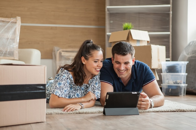 태블릿으로 장식을 계획하고 거실에서 집으로 이사하는 커플. 새 아파트로 이사하는 젊은 커플.