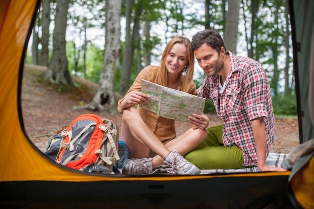 森を渡る彼らの旅行を計画しているカップル