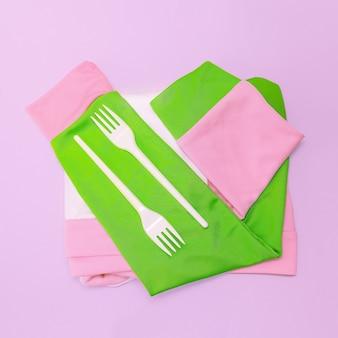 Couple plastic forks and jacket. pastel colors. minimalism vanilla art.