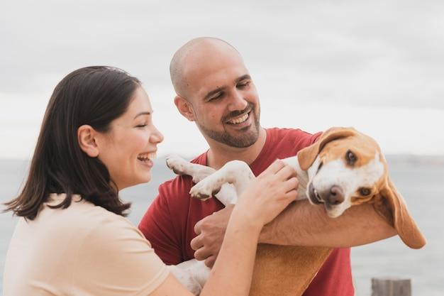 Пара playign с собакой на открытом воздухе