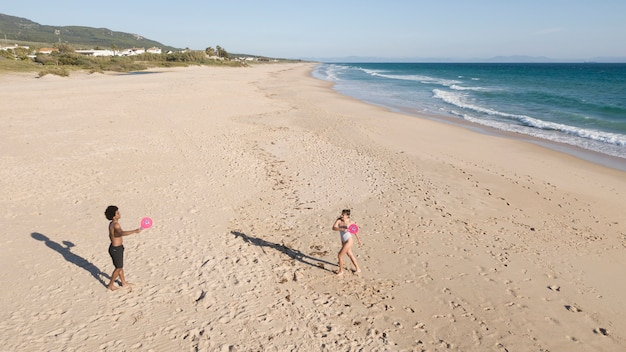 Couple playing badminton on sandy beach by sea