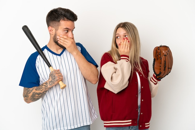 Пара играет в бейсбол на изолированном белом фоне, прикрывая рот руками за то, что сказала что-то неуместное