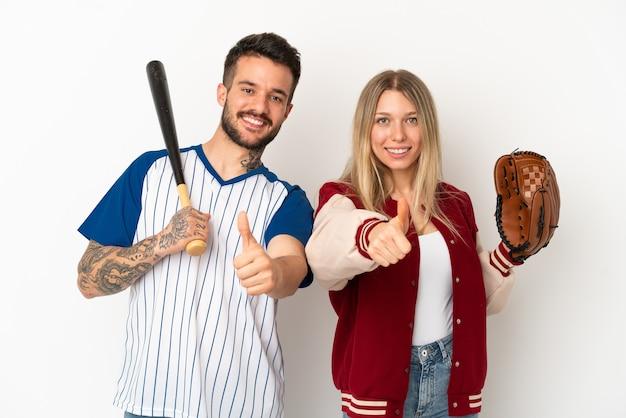 何か良いことが起こったので、親指を立てるジェスチャーを与える孤立した白い背景の上で野球をしているカップル