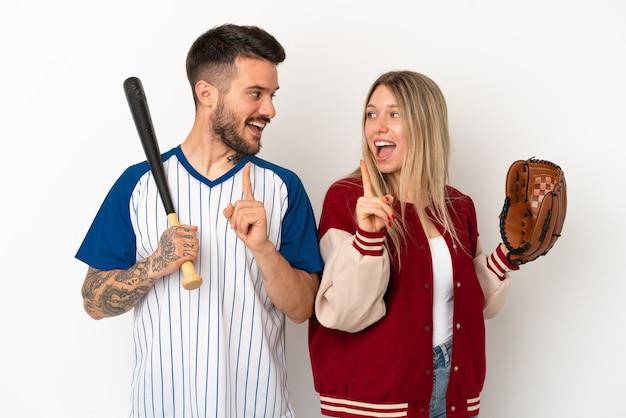 격리된 흰색 배경에서 야구를 하는 커플은 손가락을 들어올리면서 솔루션을 실현하려고 합니다.