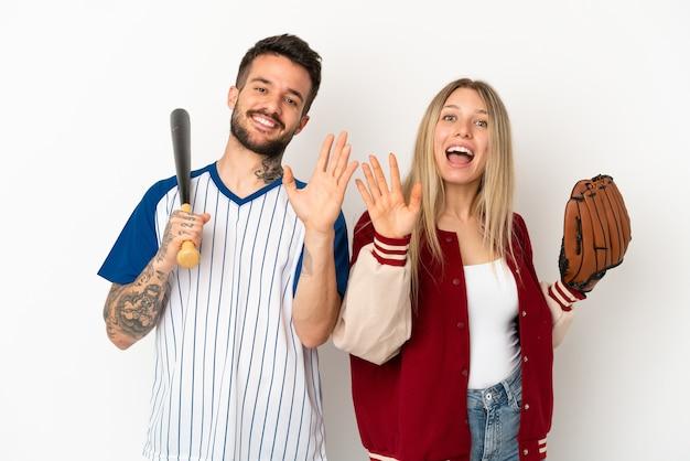 Пара играет в бейсбол на изолированном белом фоне, салютуя рукой с счастливым выражением лица