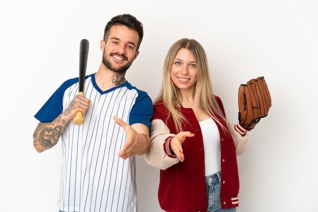 Пара играет в бейсбол на изолированном белом фоне, пожимая руку для заключения хорошей сделки