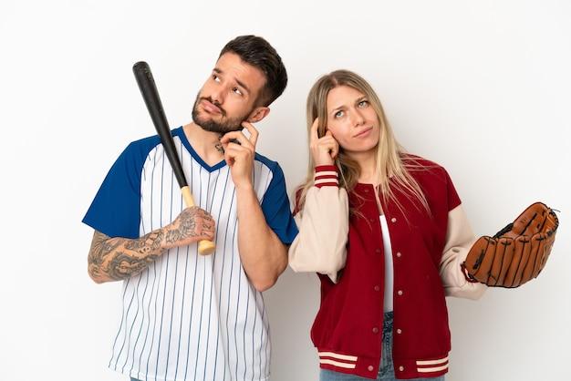Пара играет в бейсбол на изолированном белом фоне, думая об идее, почесывая голову