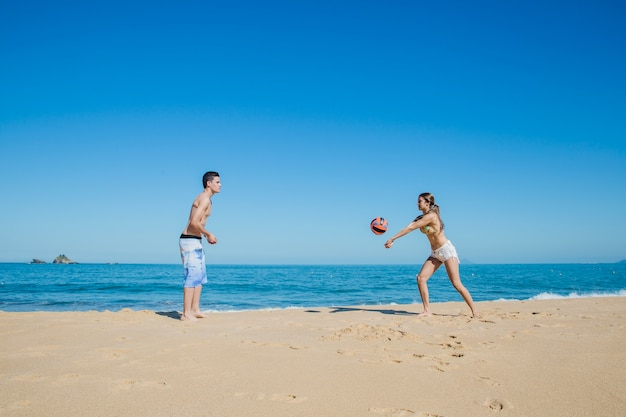Couple playing beach volleyball at the shoreline Free Photo