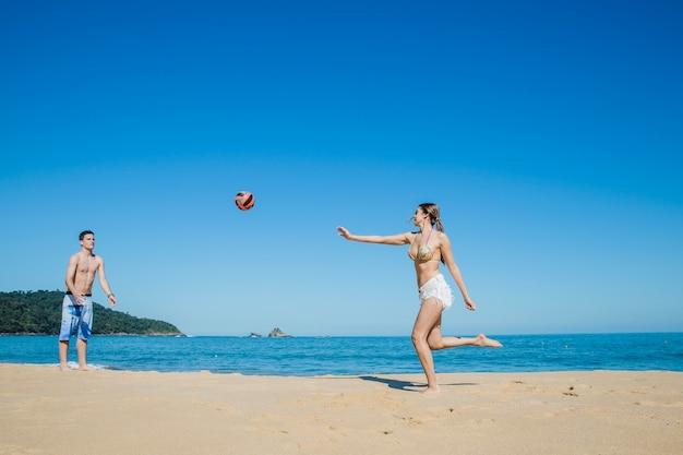 Пара играет в пляжный волейбол
