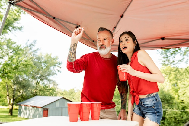 Couple playing beer pong at a tailgate party