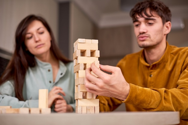 Couple playing in board game blocks at home during lockdown time